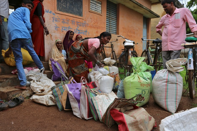 A woman ties a sack filled with subsidised food outside a fairprice shop in Seoni village, Chhattisgarh.