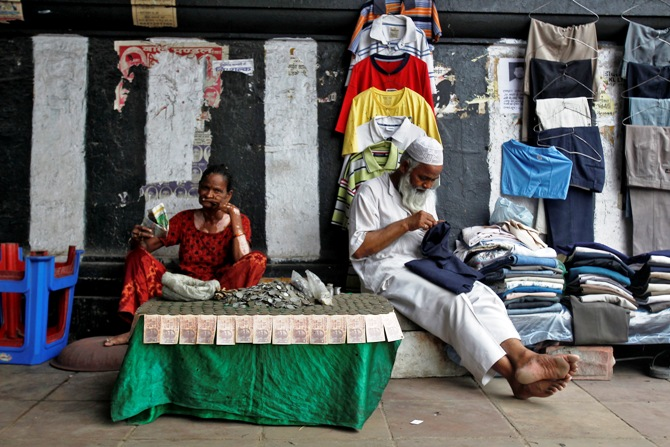 A woman exchanging damaged Indian currency waits for customers along a roadside in New Delhi.