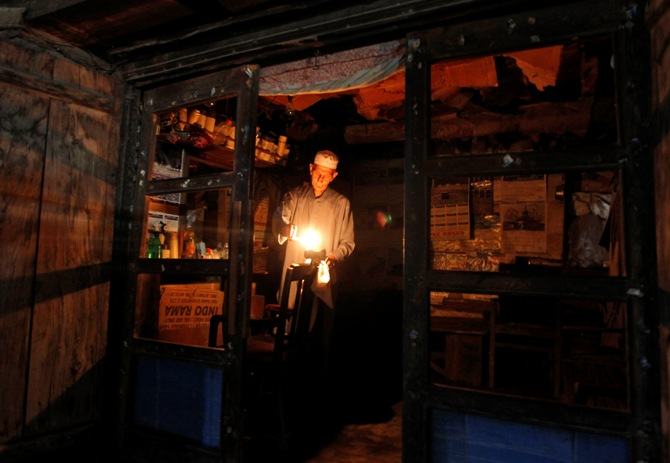 A barber lights candles after a power-cut due to curtailment, at his shop in Srinagar.