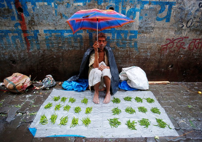 A vegetable vendor sits under an umbrella on a tarpaulin sheet at a market during monsoon rains in Mumbai.