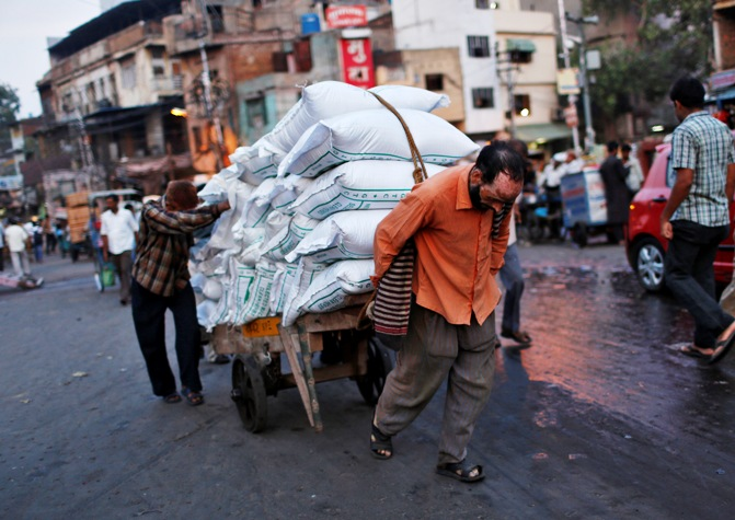 Labourers use a handcart to carry sacks at a wholesale grocery market in the old quarters of Delhi.