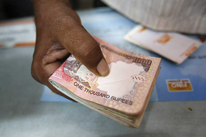 A customer hands a bundle of rupee notes to a teller at a financial institution in Mumbai.