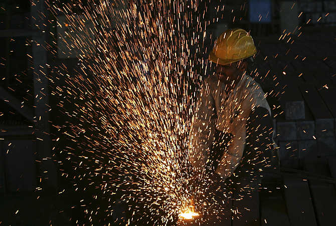 A worker cuts steel bars inside a factory on the outskirts of Hyderabad.