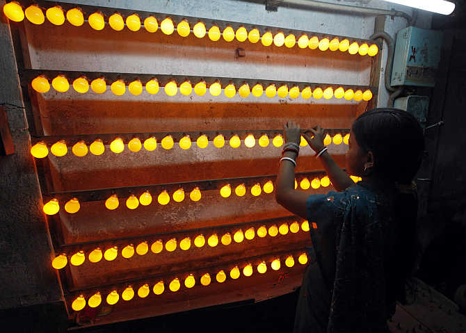 An employee works inside a bulb-manufacturing factory in Kolkata.