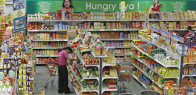 A worker of a food superstore arranges products inside a mall in Ahmedabad.