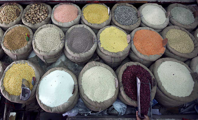 A retail trader scoops kidney beans at his shop in Jammu.