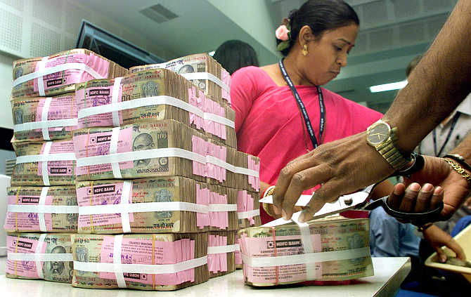 A Reserve Bank of India official opens a bundle of rupee notes.