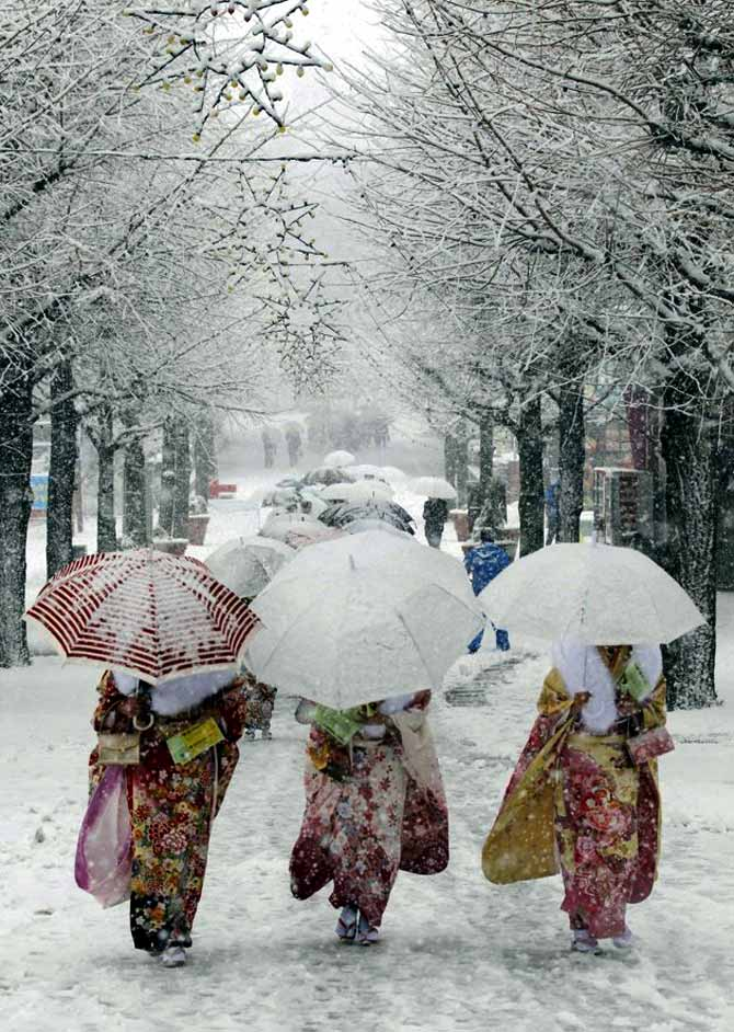 Japanese women in kimonos walk during heavy snowfall at Toshimaen amusement park in Tokyo.
