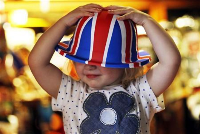 A young girl named Scarlett Rose Green tests a Union flag bowler hat in south west London.