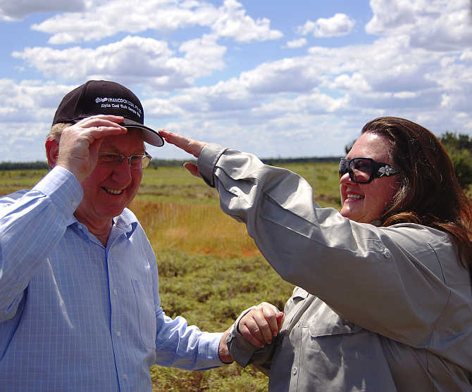 Gina Rinehart, right, adjusts a cap on the head of Australia's Minister for Resources, Energy and Tourism, Martin Ferguson in the Galilee Basin about 800km northwest of Brisbane.