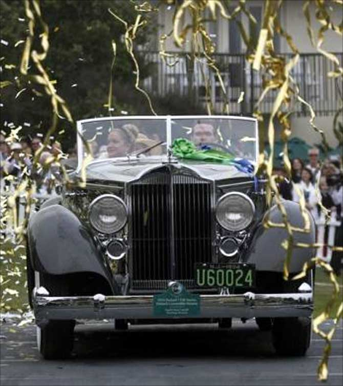 Confetti streams down as Joseph Cassini and his daughter Caroline Cassini drive on stage to receive the Best of Show award for their 1934 Packard 1108 Twelve Dietrich Convertible Victoria at the Concours d'Elegance on the 18th fairway of the Pebble Beach Golf Links in Pebble Beach, California.