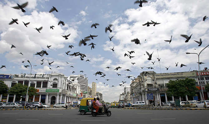 Pigeons fly as clouds gather over New Delhi's Connaught Place in India.