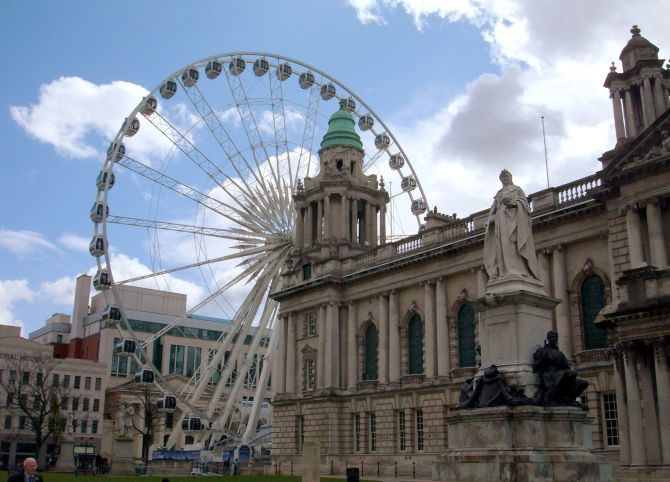 A statue of Britain's Queen Victoria at Belfast's City Hall stands close to a new 60-metre high Ferris wheel attraction, in Belfast, Northern Ireland.