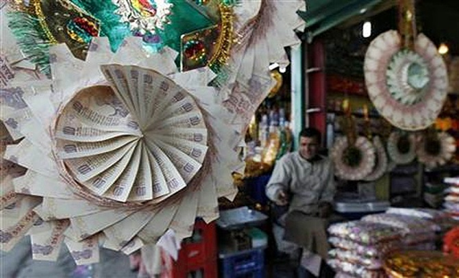 A Kashmiri shopkeeper sits near garlands made of currency notes at a market in Srinagar.