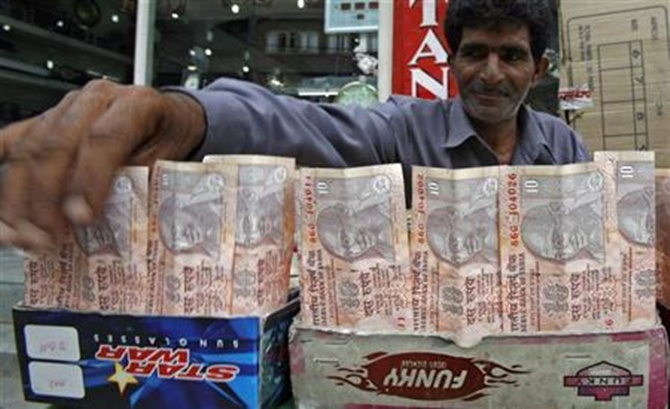 A Kashmiri money changer Nissar Ahmad displays Indian rupee notes in Srinagar.