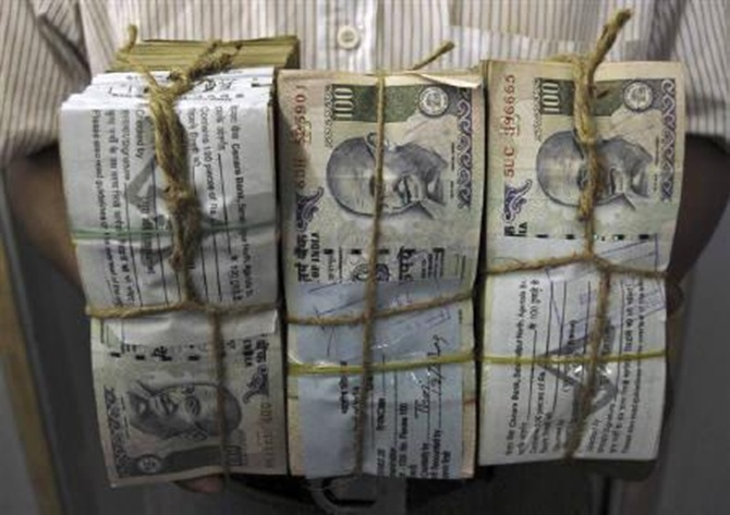 An employee carries bundles of rupee notes inside a bank in Agartala.