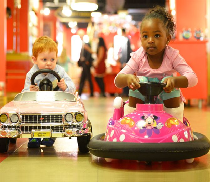 Tristan Robertson Jeyes, 2, drives a 250 pounds Sterling (383 US dollar) pink Cadillac next to Jayla Silva, 3, on a 160 pounds Sterling (244 US dollars) mini dodgem in Hamleys toy store.