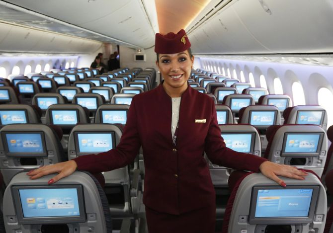 An air stewardess for Qatar Airways poses in the economy class cabin of the new Boeing 787 Dreamliner at the Farnborough Airshow.