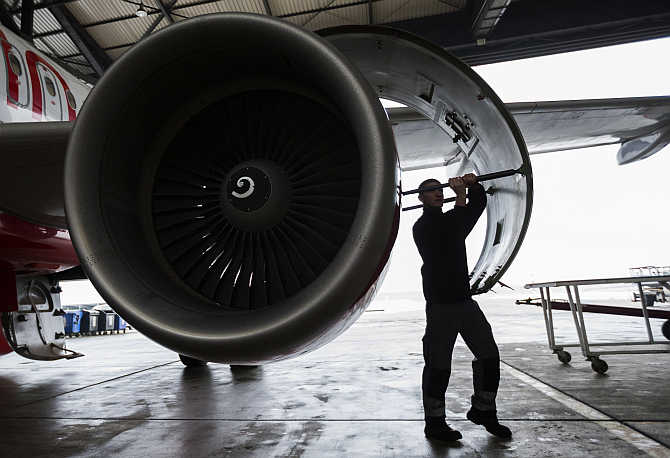 A technician opens the cover of a jet engine of an Air Berlin plane at a hangar at Tegel Airport in Berlin, Germany.