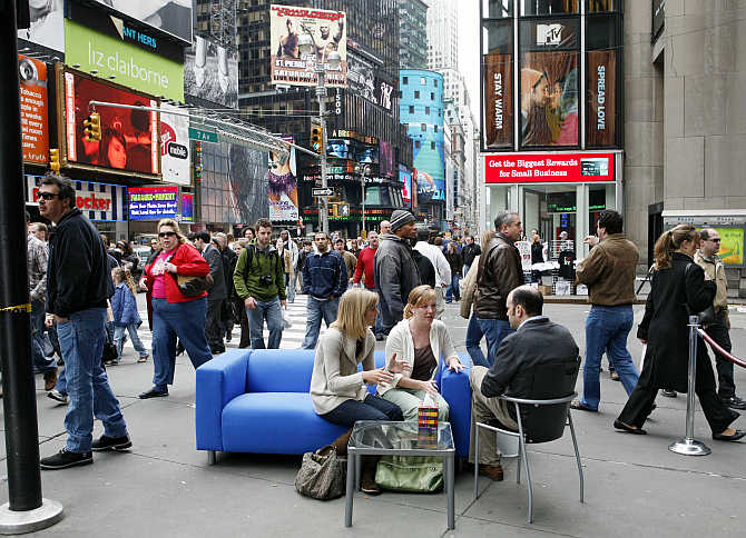 Two ladies sit and talk with the 'Good Listener' on the blue couch in New York City's Times Square. The couch will travel across the United States as Kleenex, the inventor of facial tissues, invites people to release their emotions.