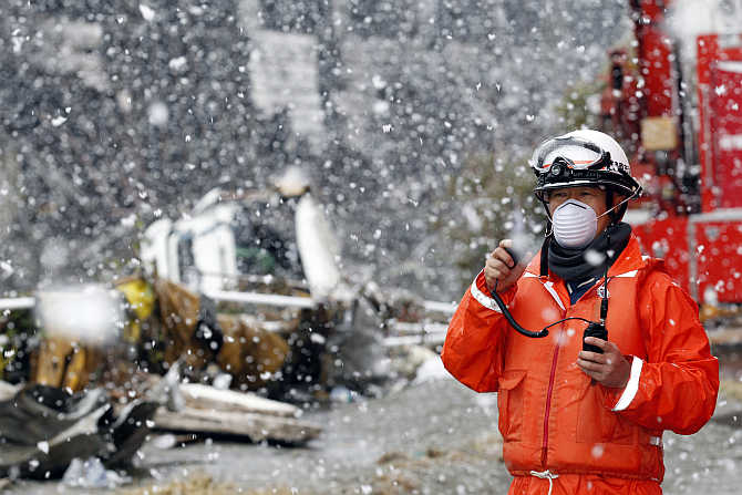 A rescue worker uses a two-way radio transceiver during heavy snowfall in Sendai, northern Japan.