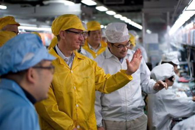 Apple Chief Executive Officer Tim Cook (2nd L) talks to employees as he visits the iPhone production line at the newly built Foxconn Zhengzhou Technology Park, Henan province.