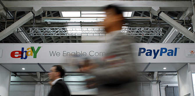 Visitors walk past an ebay banner at the Mobile World Congress in Barcelona, Spain.