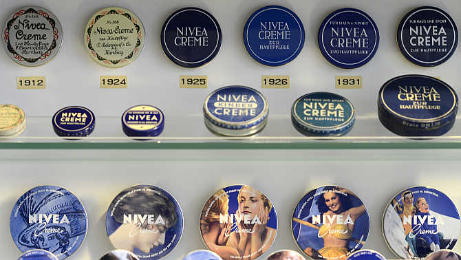 A collection of Nivea skin cream tins in a showcase beside a production line of German company Beiersdorf in Hamburg.