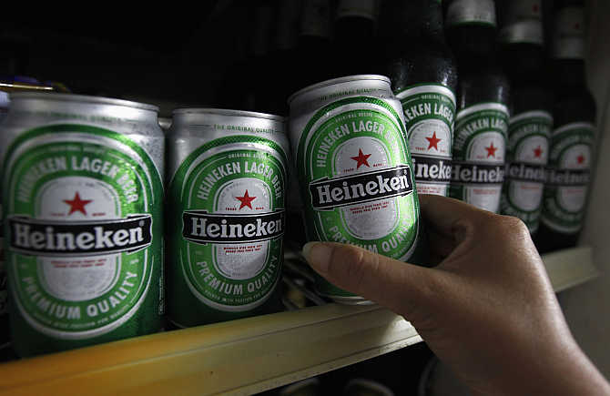 A woman reaches for a can of Heineken at a restaurant in Bangkok, Thailand.