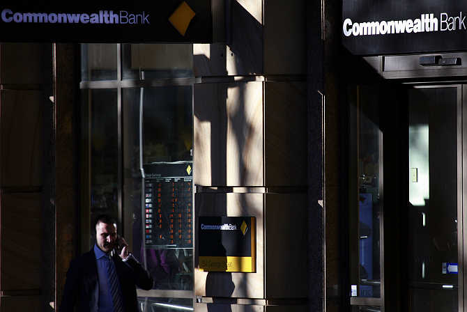 A man talks on his mobile phone as he walks past a Commonwealth Bank branch in central Sydney.