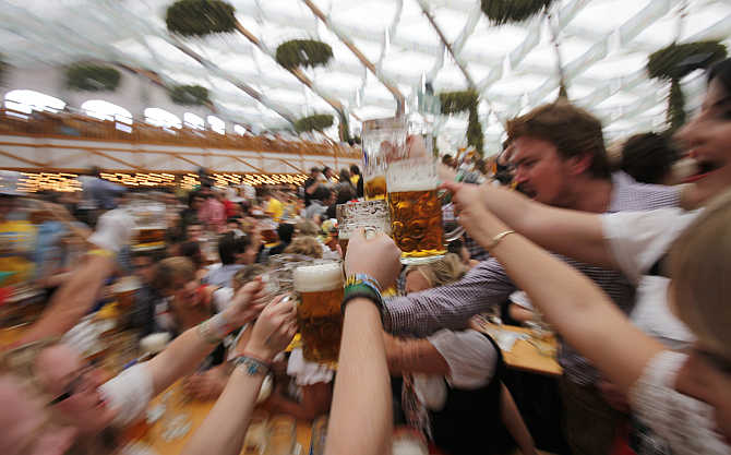 People wearing traditional Bavarian clothes toast with beer during the opening day of the Oktoberfest in Munich, Germany.