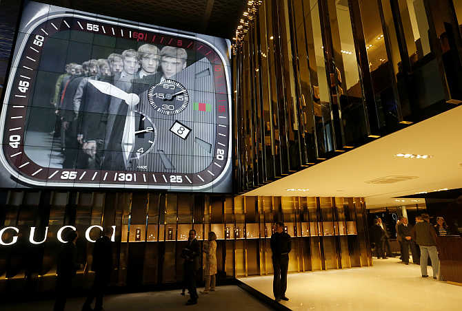 People walk at the exhibition stand of Gucci at Baselworld fair in Basel, Switzerland.