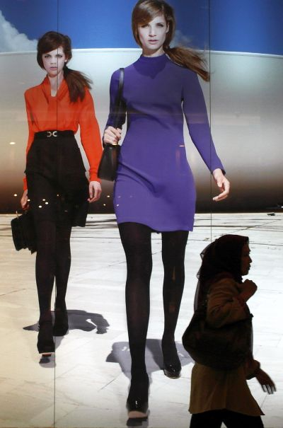People walk past a fashion brand's advertisement at a shopping mall.