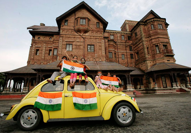 Children hold Indian national flags as they sit on a car during a photo-shoot in front of Hari P