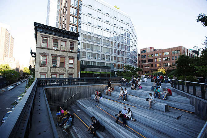 Pedestrians sit in a viewing area on the High Line park in New York City, United States.