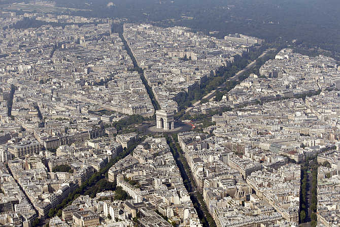 An aerial view shows the Arc de Triomphe, centre, at the centre of the Place Charles de Gaulle and rooftops of residential buildings in Paris, France.