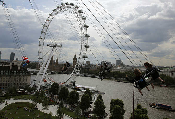 Thrill seekers ride a fairground attraction overlooking the London Eye, Houses of Parliament and the Thames river in London, United Kingdom.