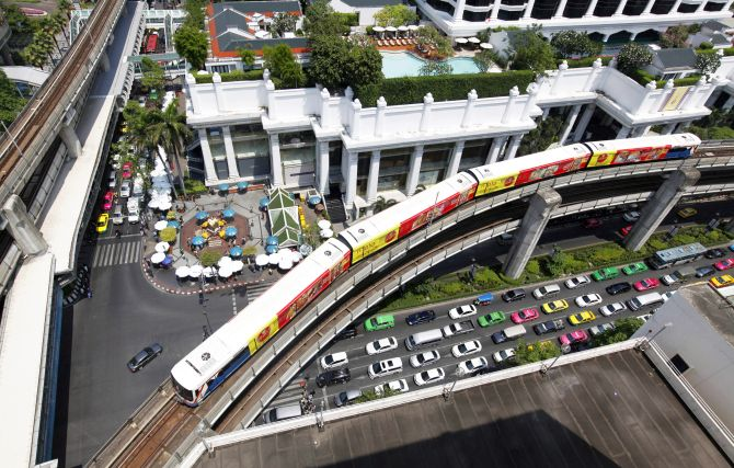 A skytrain passes over vehicles on the road in Bangkok.