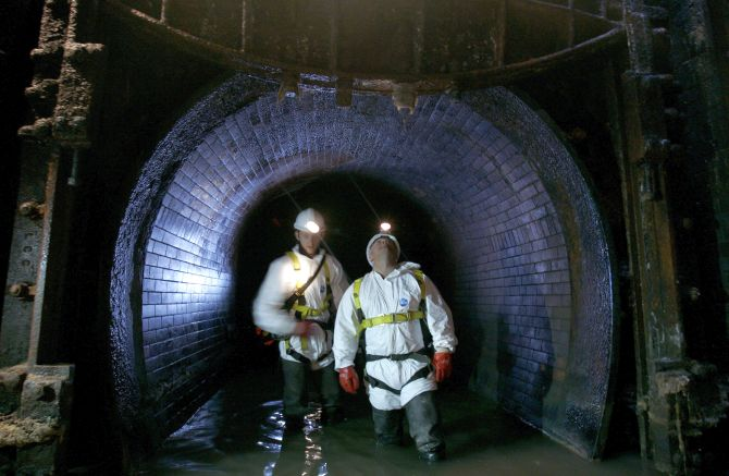Sewer inspectors, known as flushers, demonstrate looking for damage and leaks in the sewerage system during a media facility, London.