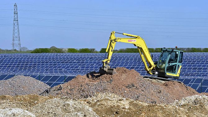 Construction work is seen at a field of solar panels in southern England.