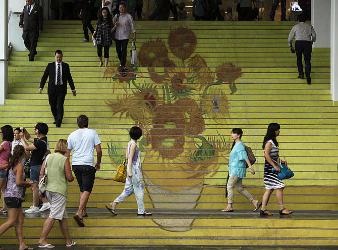 People walk on stairs featuring a five-metre-high reproduction of Vincent van Gogh's signature painting 'Sunflowers', at the entrance to Ocean Terminal in Hong Kong.
