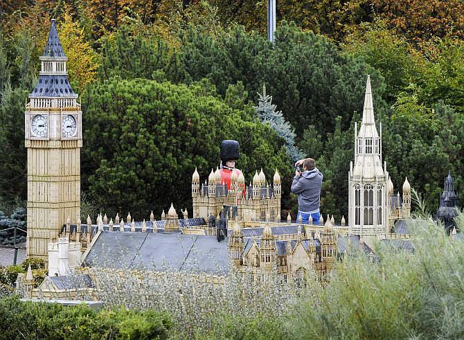 A tourist takes a picture of a model of an English guard in front of a miniature reproduction of the Buckingham Palace in the Mini-Europe park, where all the models are built at a scale of 1:25, in Belgium, Brussels.