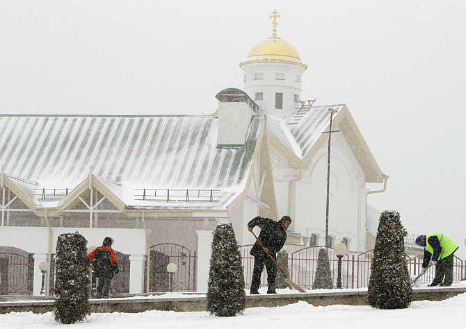 Workers of an Orthodox church clear snow from a pavement in front of the church during heavy snowfall in central Minsk, Belarus.