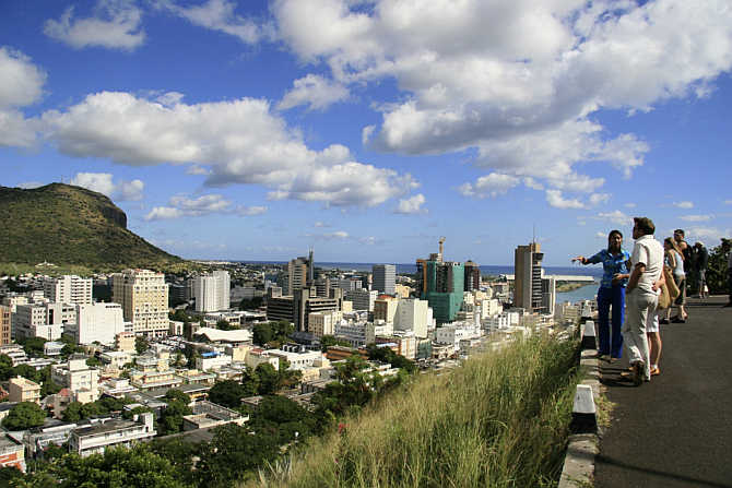 A tour guide stands with a group of tourists at a viewpoint overlooking Port Louis in Mauritius.