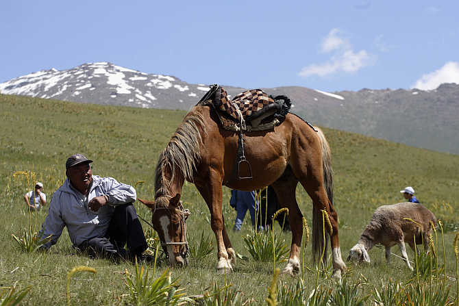 A man and his horse rest in Susamyr, Kyrgyzstan.