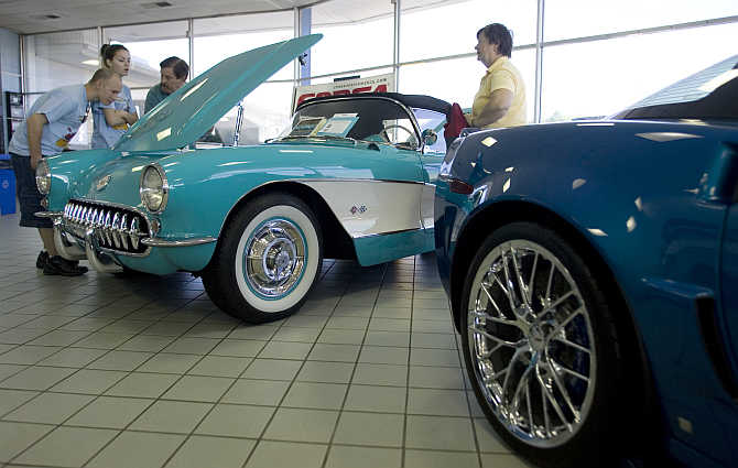 Mary Lou Gilbert, right, talks to car show attendees who are inspecting her restored 1957 Chevrolet Corvette, left, at an antique car show in Silver Spring, Maryland, United States.