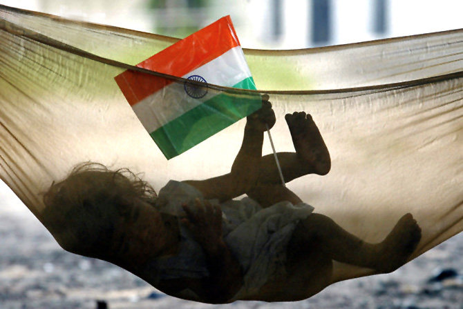 A child plays with Indian national flag while lying in hammock in a slum in Chandigarh.