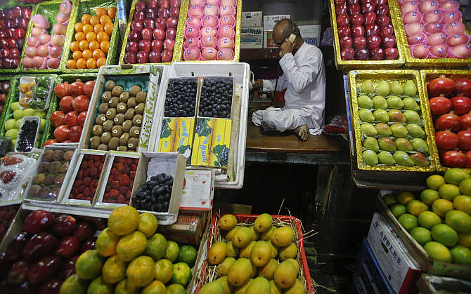 In recent times, prices of many food items have more than doubled. A fruit vendor speaks on his phone.