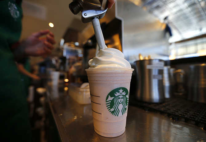 A barista puts whipped cream on a drink at Starbucks coffee shop in Fountain Valley, California.
