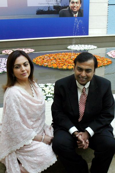 Mukesh Ambani (R), chairman of Reliance Industries, poses with wife Nita before a news conference in Mumbai.